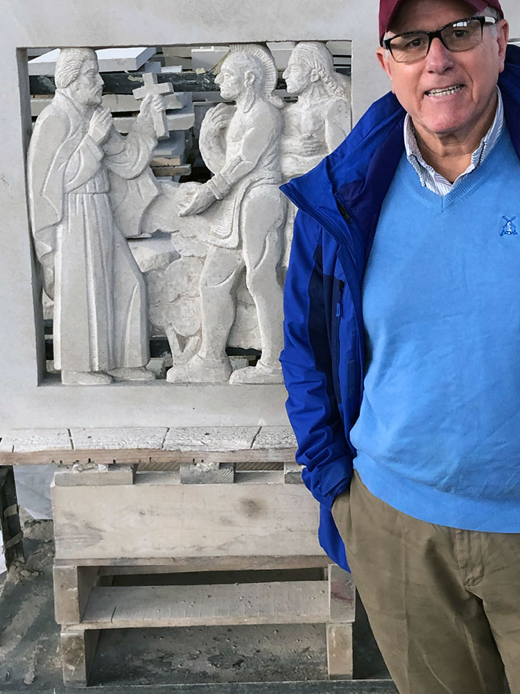 Ralph Petrillo standing next to a carving of Ignatius Loyola